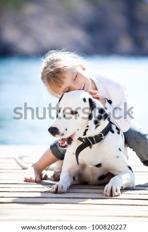 Happy baby girl with her dog on berth in summer - stock photo