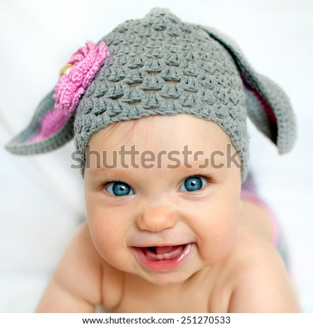 Happy baby in the hat like a bunny or lamb - stock photo