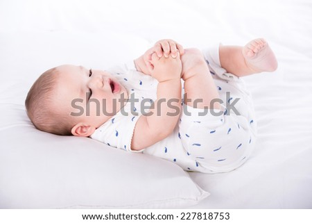 Happy baby is playing with his feet, lying on the bed. - stock photo