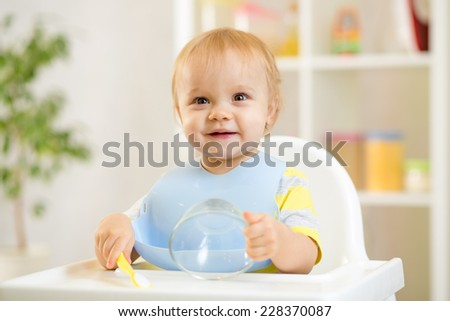 happy baby kid boy waiting for food with spoon at table - stock photo