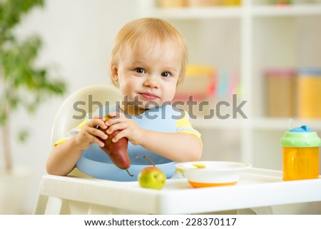 happy baby kid child boy eating fruits at highchair - stock photo