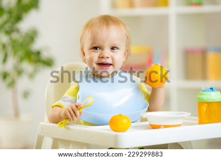 happy baby kid child boy eating healthy food at home - stock photo