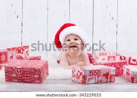 happy baby laying  among the christmas gifts - stock photo