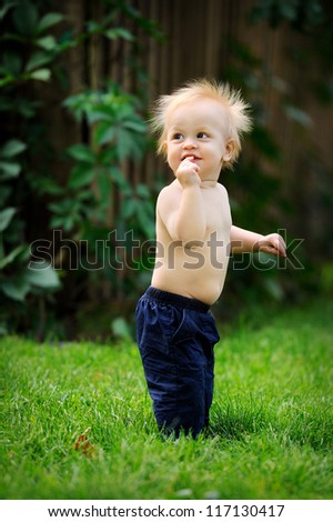 Happy baby learning to walk. He smiles and laughs. Hot summer day. - stock photo