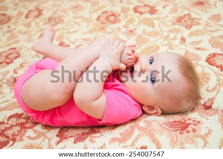 happy baby lying  and holding his legs - stock photo