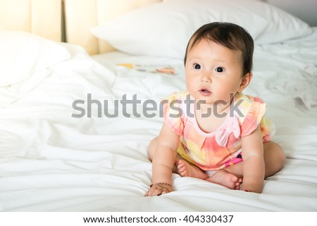 happy baby lying on bed - stock photo
