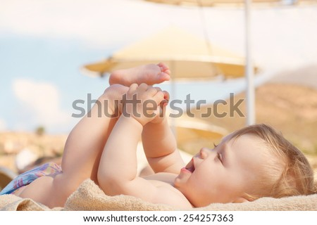 Happy baby on the beach sunbed. 8 month old kid lying on a sun lounger and playing with her feet. Summer holidays concept. - stock photo
