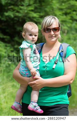 Happy baby on the mother's hands in the summer park - stock photo