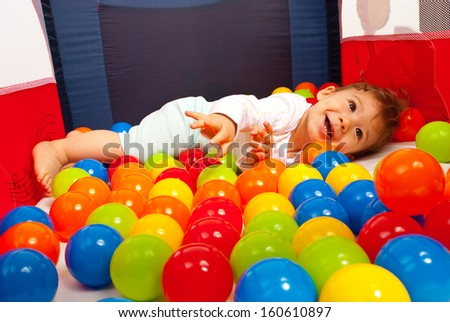 Happy baby playing with balls inside playpen - stock photo