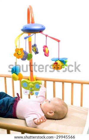 Happy baby playing with bed side toy, smiling, isolated on white background. - stock photo