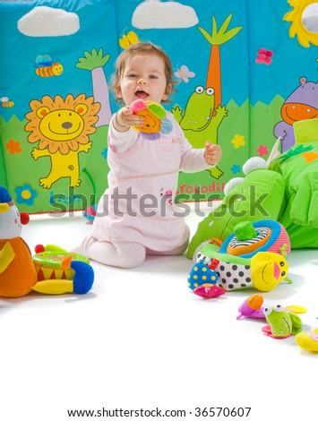 Happy baby playing with soft toys, smiling, isolated on white background. - stock photo