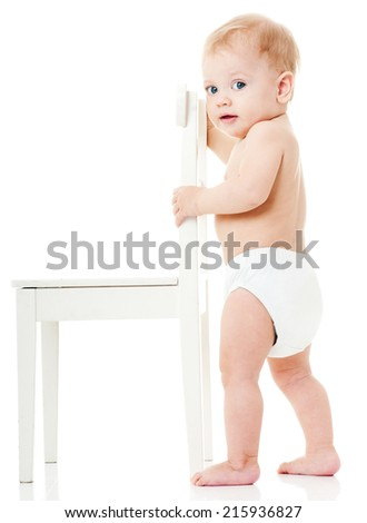 happy baby playing with white chair - stock photo