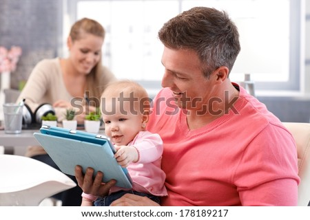 Happy baby reading e-book, sitting on father's lap, mother sitting at background. - stock photo