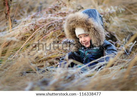 happy baby sitting in the snowy street. Autumn cold day - stock photo