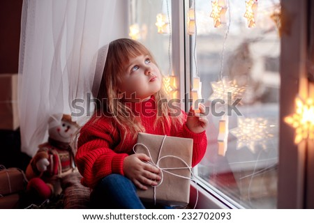 happy baby sitting on the window with Christmas present - stock photo