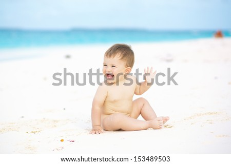 Happy baby smiling and waving hand, sitting on white sandy tropical beach  - stock photo