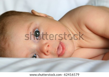 Happy baby smiling on white sheets - stock photo