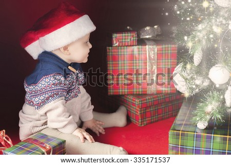Happy baby surprised near the decorated Christmas tree with many gift and present box! Kid dressed in red Santa hat. Xmas and New Year holiday! - stock photo