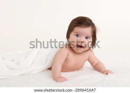 happy baby under white towel - stock photo