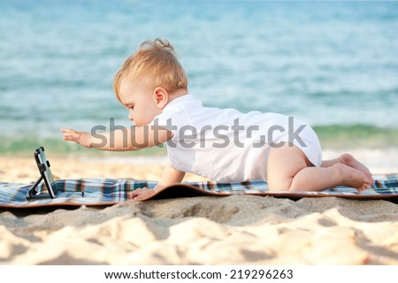 Happy baby with a tablet pc on the beach. Summer holidays concept. Toddler wearing a white t-shirt, ready for symbol. - stock photo