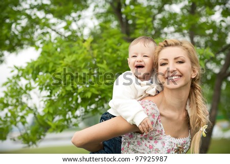 happy baby with mother on a background of green leaves. Much of copyspace - stock photo
