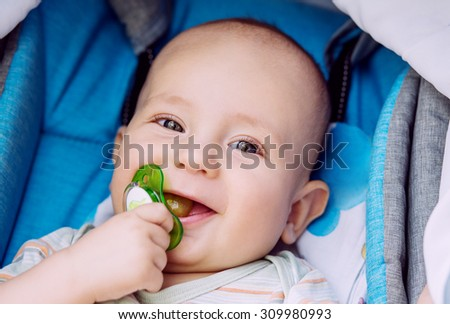 happy baby with pacifier lying in a stroller - stock photo