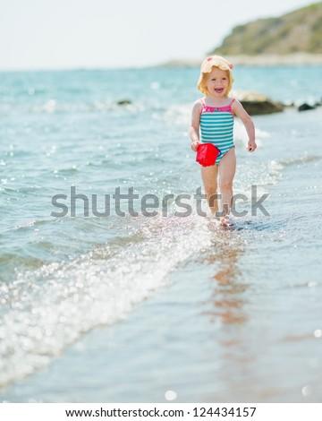 Happy baby with pail running along seashore - stock photo