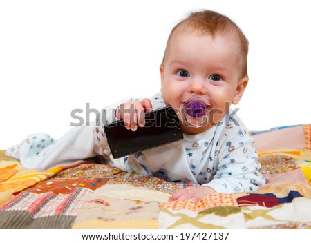 happy baby with telephone lies on bed suck pacifier on a white background - stock photo