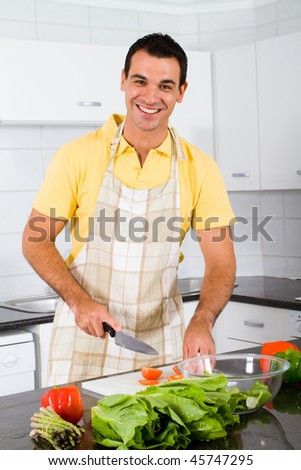 happy bachelor cooking in kitchen - stock photo