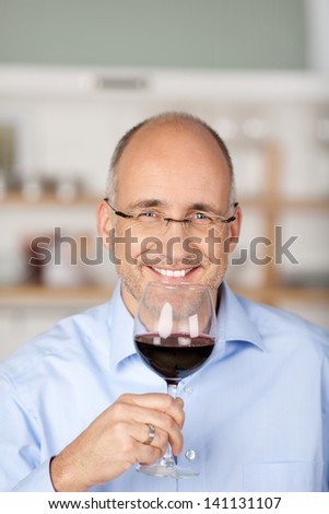 Happy bald man holding a glass of red wine - stock photo