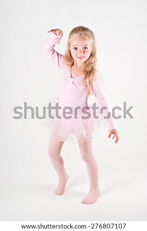 Happy ballet dancing little girl in pink dress on the light background - stock photo
