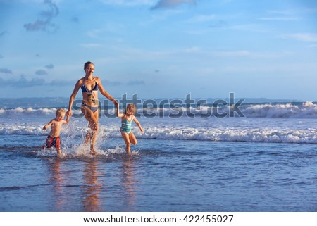 Happy barefoot family having fun - mother, baby son, daughter together run with splashes by water pool along surf of sunset sea beach. Active parents,  people activity on summer holiday with children - stock photo