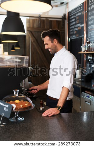 Happy barista grinding coffee at cafe - stock photo