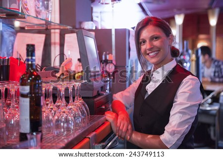 Happy barmaid using touchscreen till in a bar - stock photo