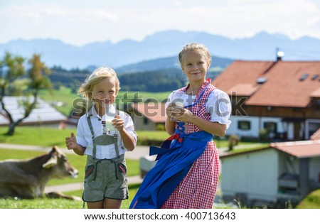 Happy Bavarian children drink milk on the meadow with cow . Alps in background . Germany . - stock photo