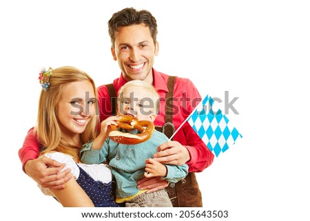 Happy bavarian family smiling with pretzel and flag - stock photo