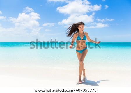 Happy beach summer fun Asian bikini woman running of joy on amazing white sand enjoying holidays on Caribbean tropical travel to paradise destination. Cheerful young girl on exotic getaway vacation. - stock photo