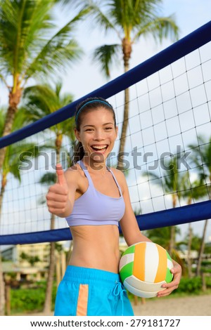 Happy beach volleyball woman player thumbs up. Excited smiling woman holding beach volley ball giving thumbs up success hand sign looking at camera. Mixed race Asian Caucasian woman athlete. - stock photo