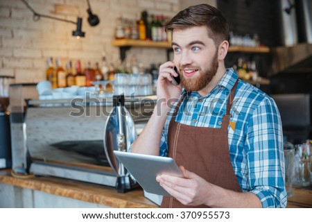 Happy bearded young waiter talking on cell phone and using tablet in cafe - stock photo