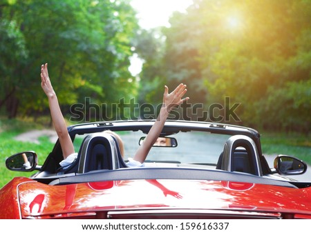 Happy beautiful blond young woman driving a sports car - stock photo