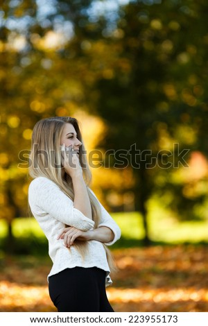 happy beautiful blonde girl talking over the phone and smiling in autumn outdoors - stock photo