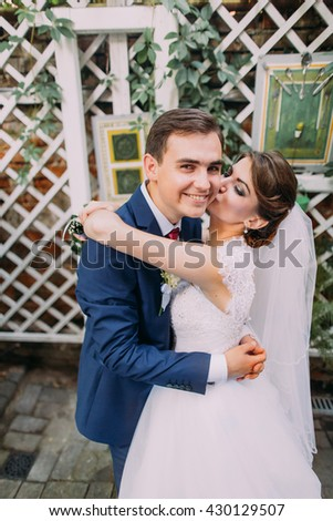 Happy beautiful bride and groom embracing after their wedding ceremony. Close-up - stock photo