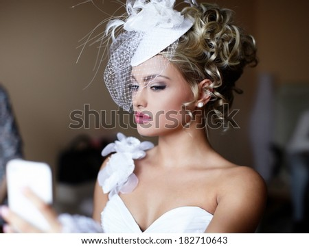 Happy beautiful bride blond girl in white wedding dress with hairstyle and bright makeup on home background looking in the mirror - stock photo