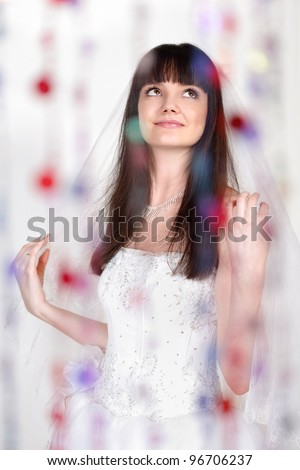 Happy beautiful bride looks up behind transparent curtain of beads; focus on woman - stock photo