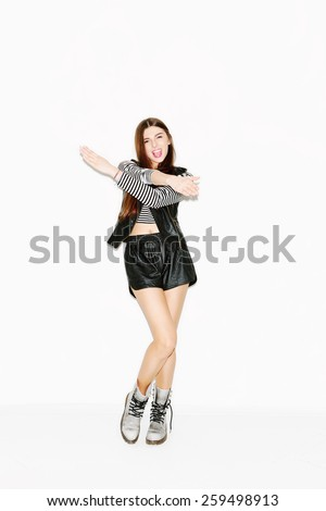 Happy beautiful brunette girl dancing and laughing. Slim figure, makeup, long hair. White background, not isolated. inside - stock photo