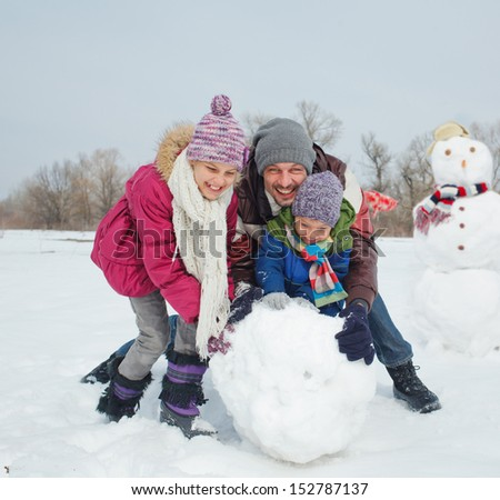 Happy beautiful children with father building snowman outside in winter time - stock photo