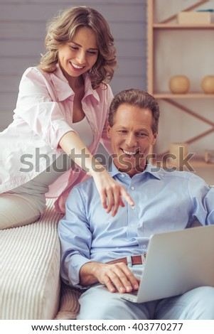Happy beautiful couple is using a laptop, cuddling and smiling while sitting on sofa at home - stock photo