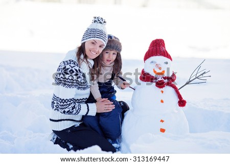 Happy beautiful family building snowman in garden, winter time, mom and kid - stock photo