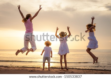 Happy beautiful family dancing on the  beach on the  dawn time. - stock photo