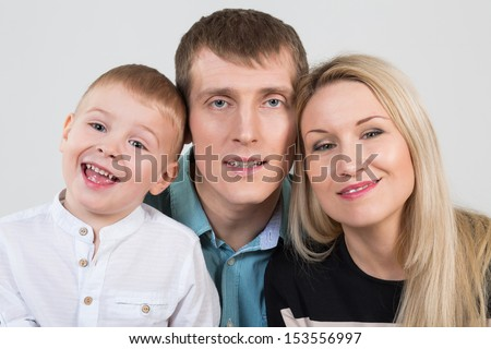 Happy beautiful family of three, son laughs in studio - stock photo
